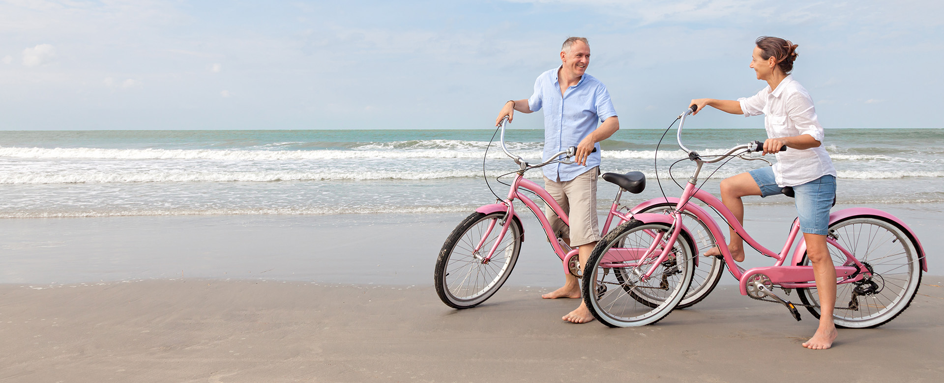 Mature couple riding bikes outdoors on beach at sunset